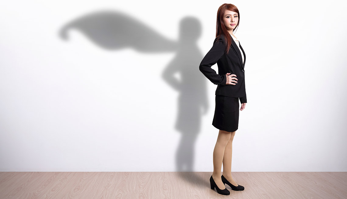 Joven vestida con traje de oficina con una sombra que tiene su figura y una capa voladora - Becas universitarias inusuales