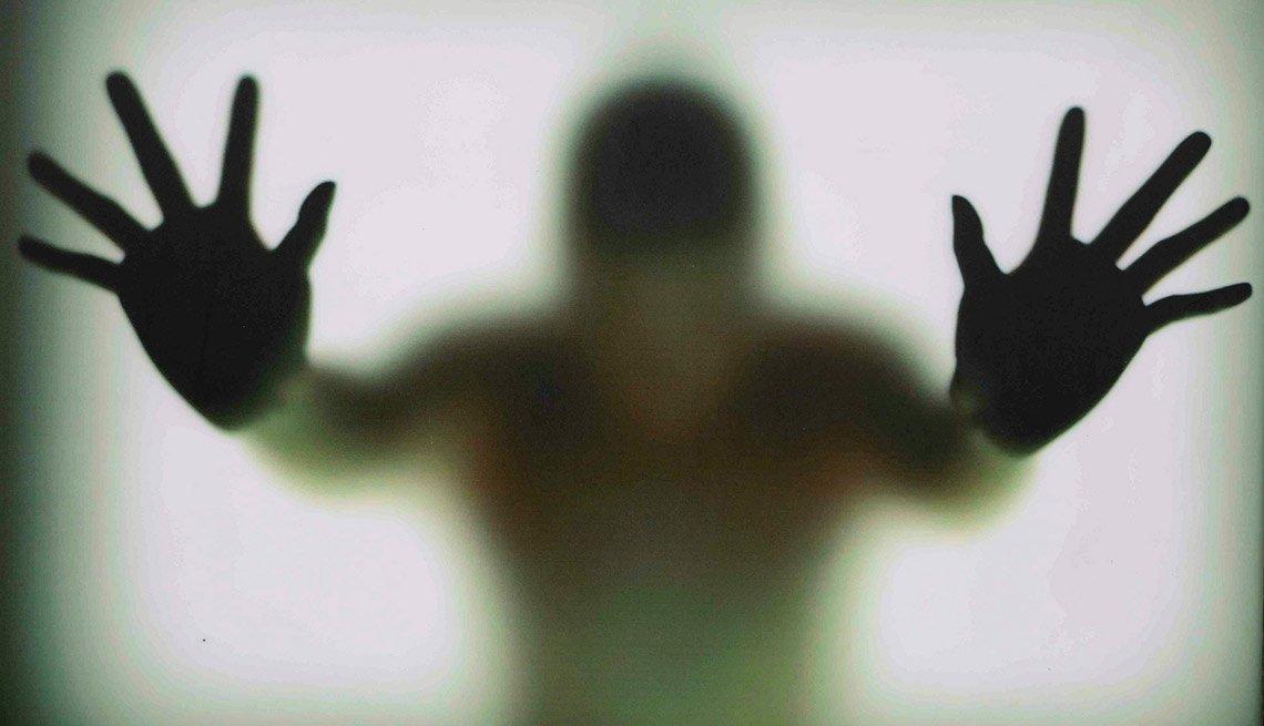 Manos de una persona apoyadas sobre un vidrio opaco - Becas universitarias inusuales