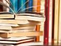 Estantería de libros con tomos en fila y otros acostados - Vende tus libros viejos