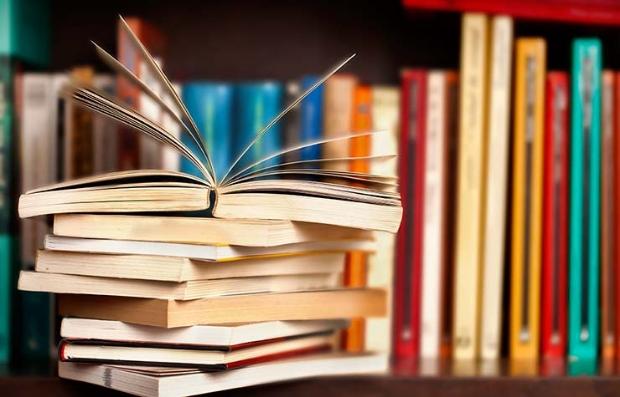 estantera de libros con tomos en fila y otros acostados vende tus libros viejos