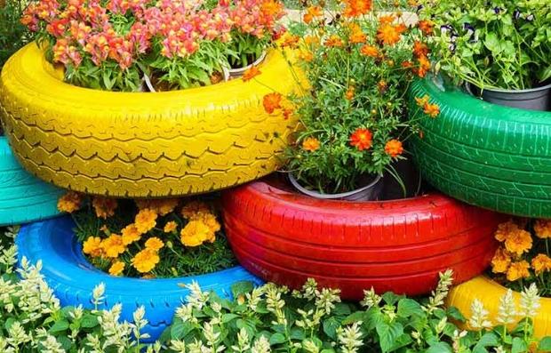Llantas viejas de automóvil pintadas que pueden usarse para la jardinería en el patio de tu casa como reciclaje mejorado