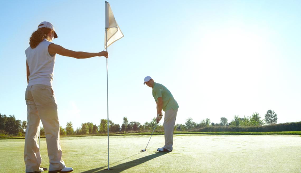 Una pareja en un campo de golf, y no te olvides de los descuentos de cumpleaños