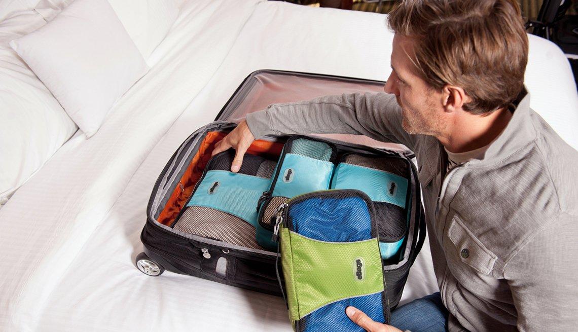 Hombre empacando maletas con separadores internos - Mejores maneras de gastar $200