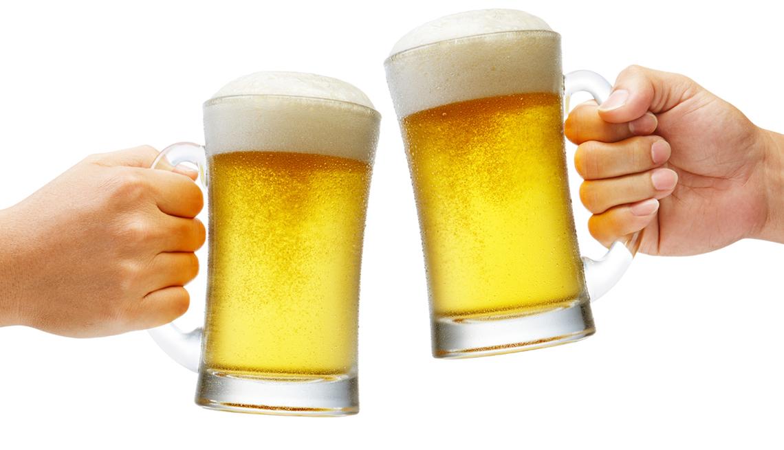 Manos sosteniendo vasos con cerveza, y no te olvides de los descuentos de cumpleaños