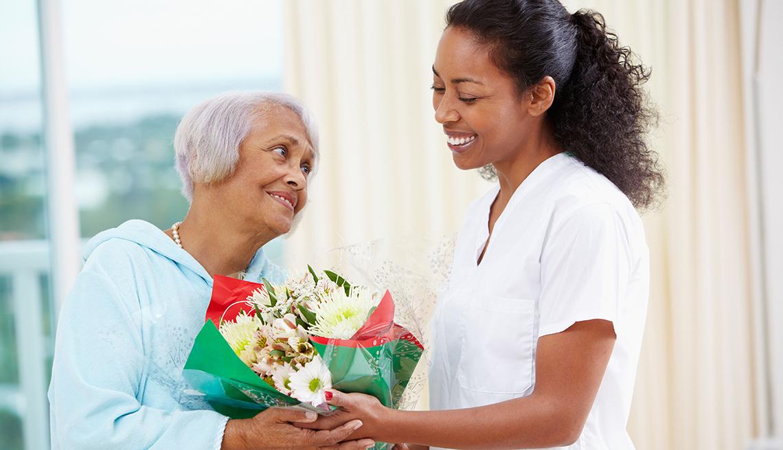 Enfermera dando un ramo de flores a una mujer mayor. Aprende a planear con tiempo el cuidado de salud a largo plazo