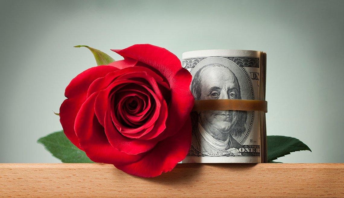 Una rosa al lado de un fajo de dólares envueltos