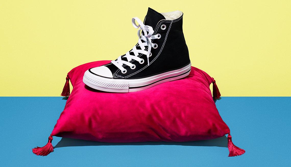 Zapato deportivo en tela de talla pequeña sobre un cojín de color rojo, para aquellos adultos que los pueden usar y ahorrar dinero
