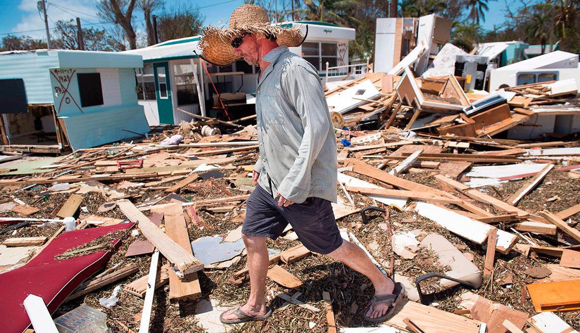 Hombre caminando sobre escombros dejados por el huracán.