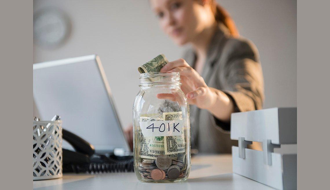 Mujer colocando dinero en un frasco de vidrio marcado con 401K - Cómo ahorrar 10 mil dólares al año