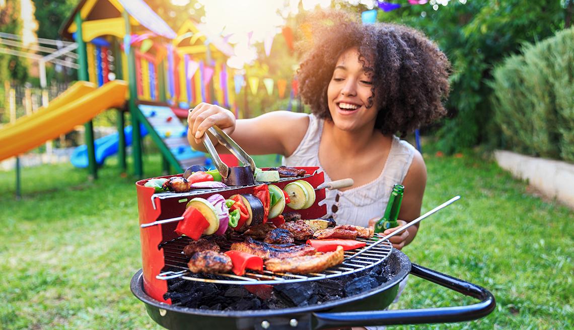 Joven afroestadounidense frente a un asador de carne en un parque - Cómo ahorrar 10 mil dólares al año