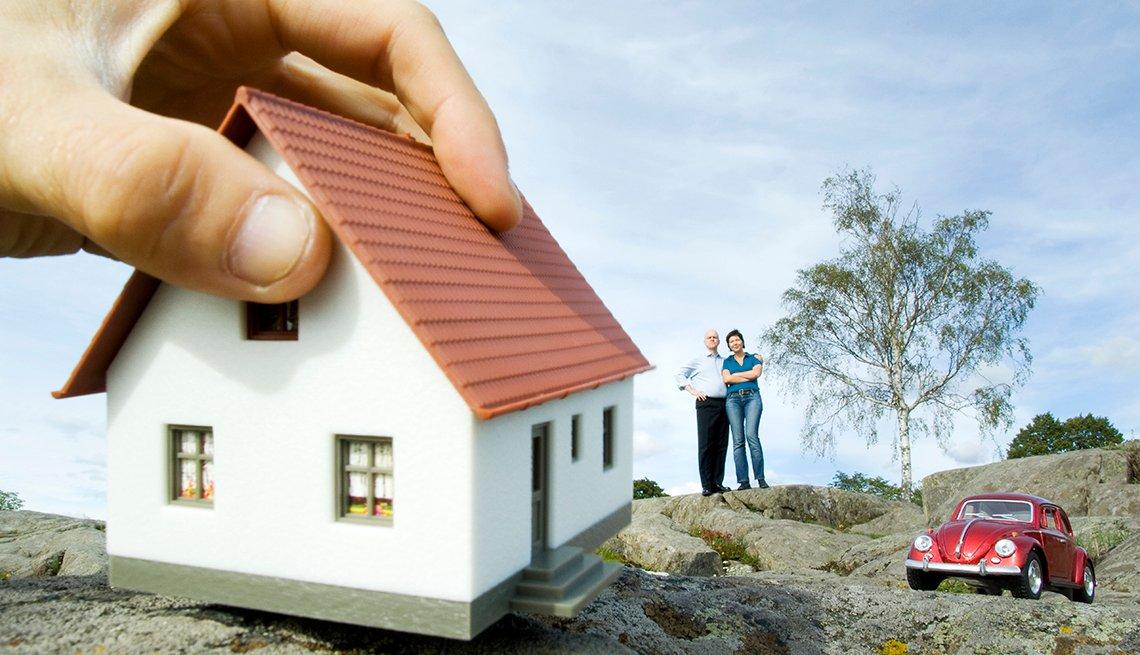 Montaje de una mano agarrando una vivienda y consejos para comprar casa