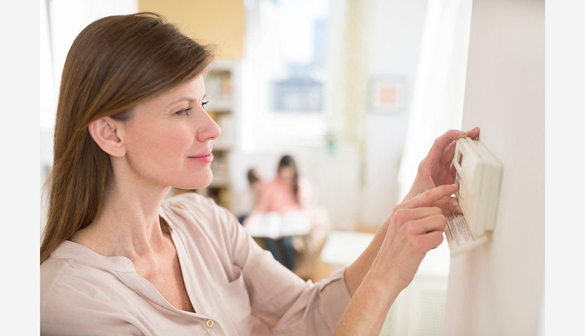 Mujer mirando el termostato de su casa - Cómo ahorrar 10 mil dólares al año