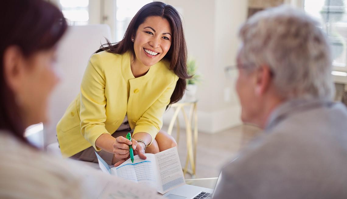 Una mujer mostrando un folleto a una pareja mayor