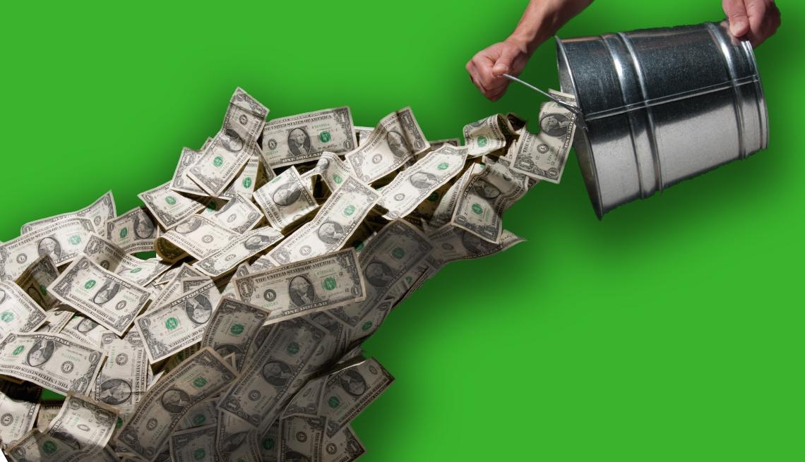 Dinero cayendo desde un balde metálico