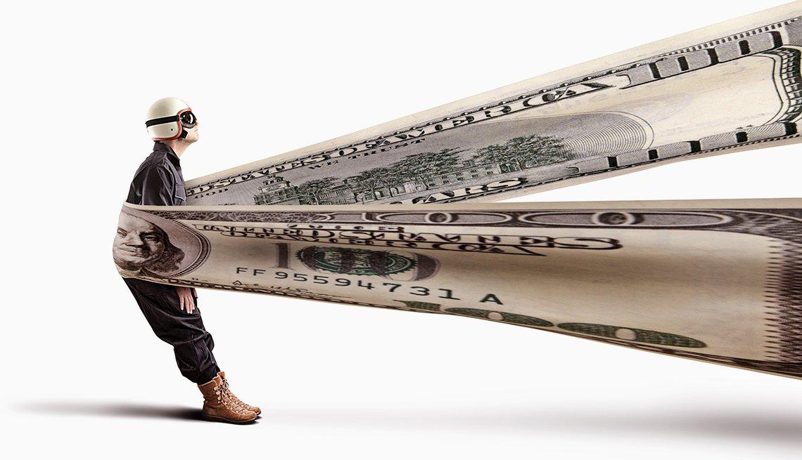 Hombre con casco y gafas a punto de ser proyectado por un billete de 100 dólares elástico