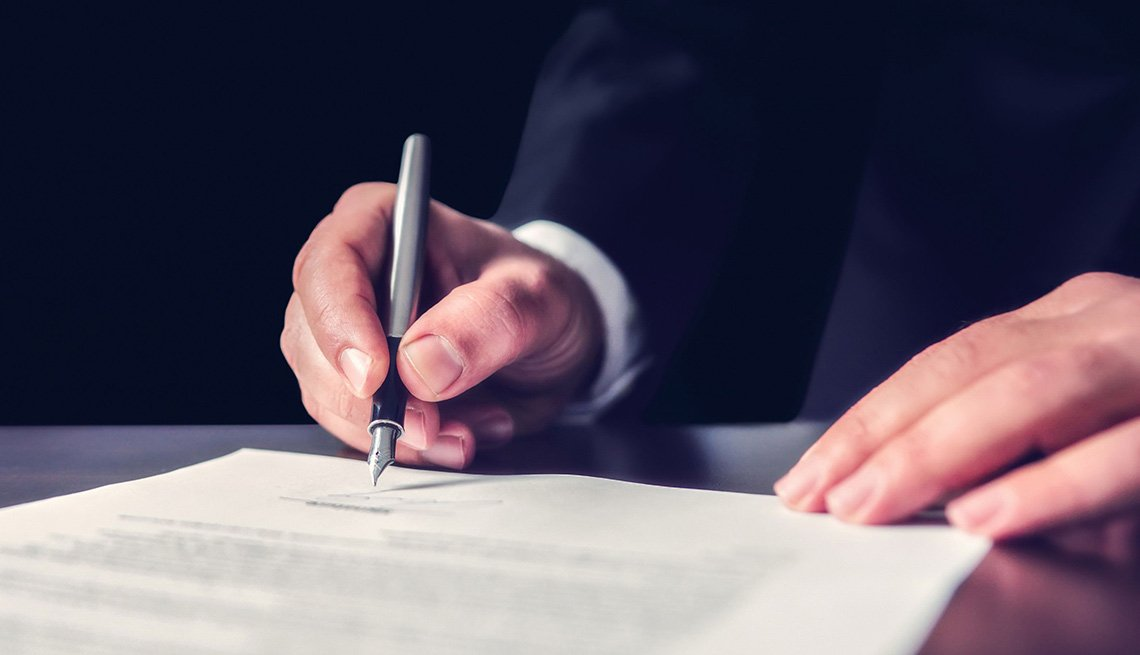 hands signing a document