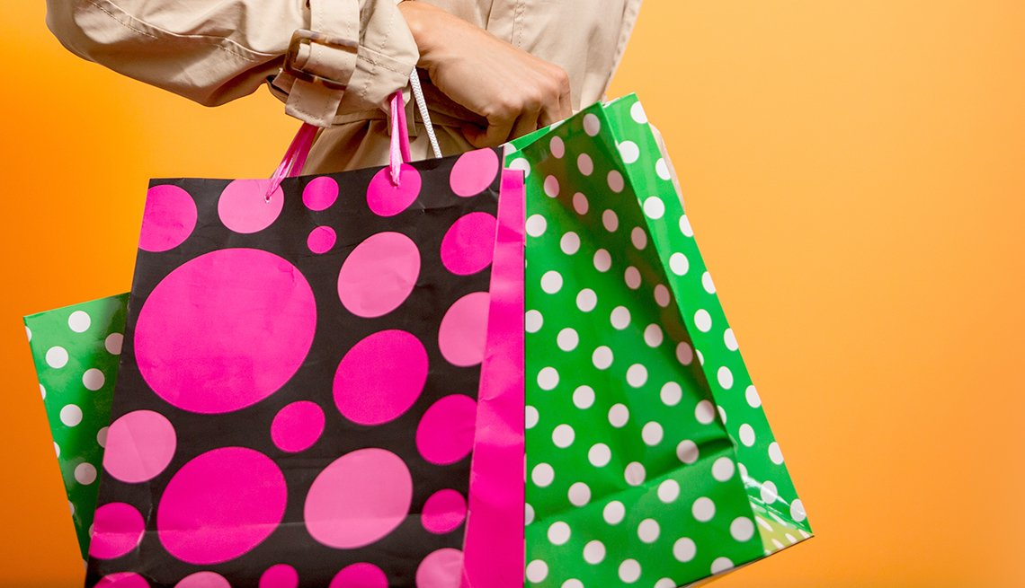 woman carries colorful shopping bags