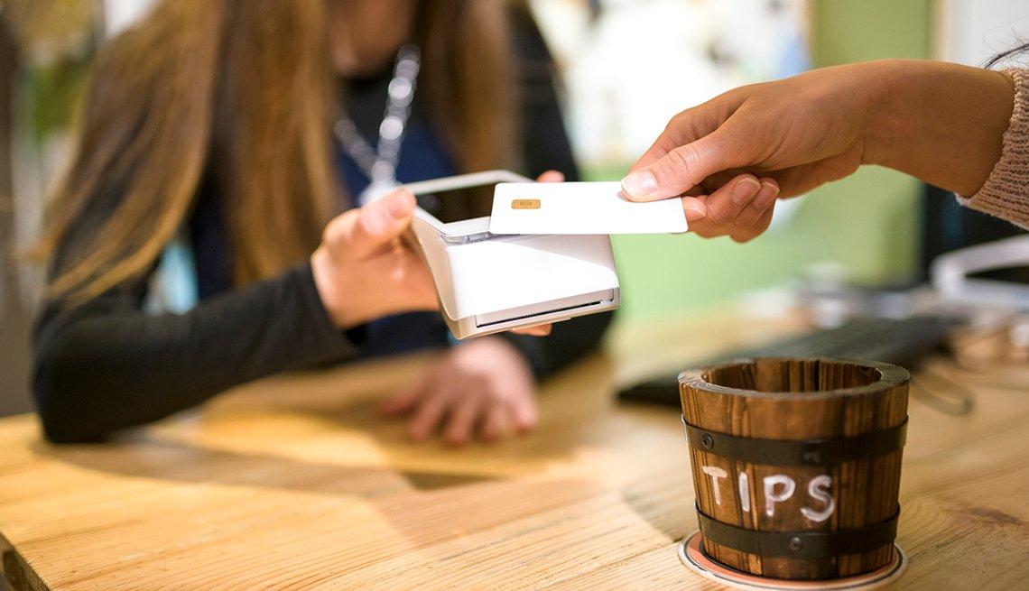 Mano de una mujer sosteniendo un teléfono mientras otra pasa una tarjeta, al aldo de un recipiente para propinas