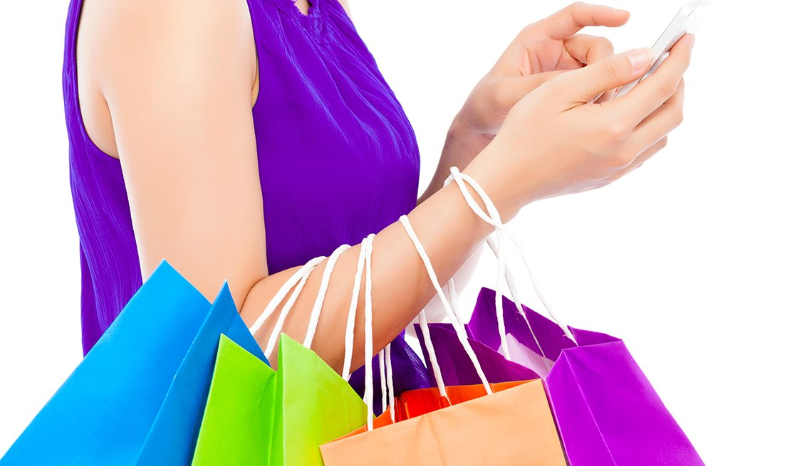 woman holding shopping bags and tapping on an iphone