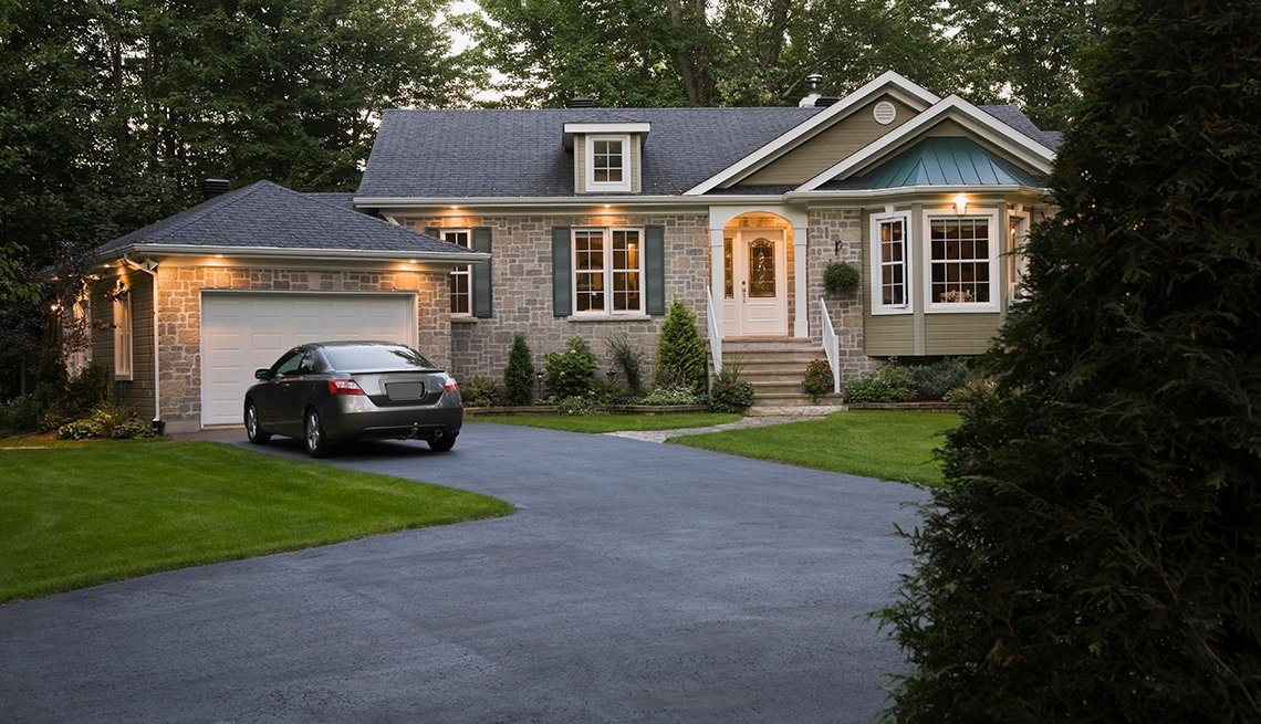 item 7, Gallery image. Brown, beige and gray stone residential home and landscaped front yard illuminated at dusk, Quebec, Canada. This image is property released. CUPR0215