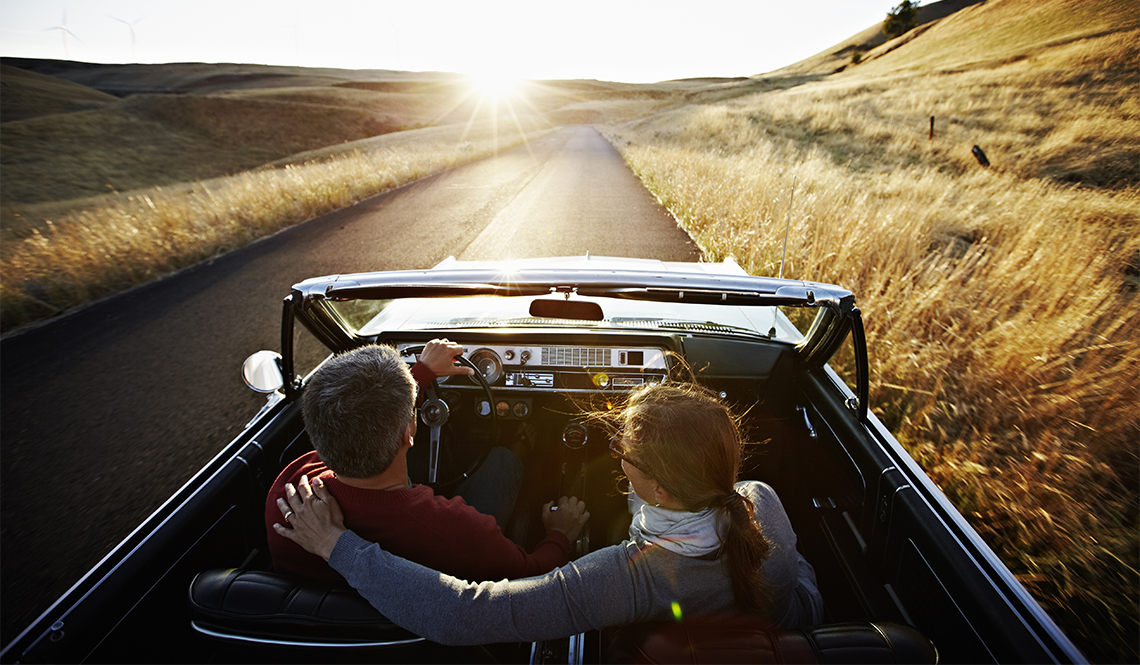 item 12 of Gallery image - Man and woman driving in a convertible at sunset