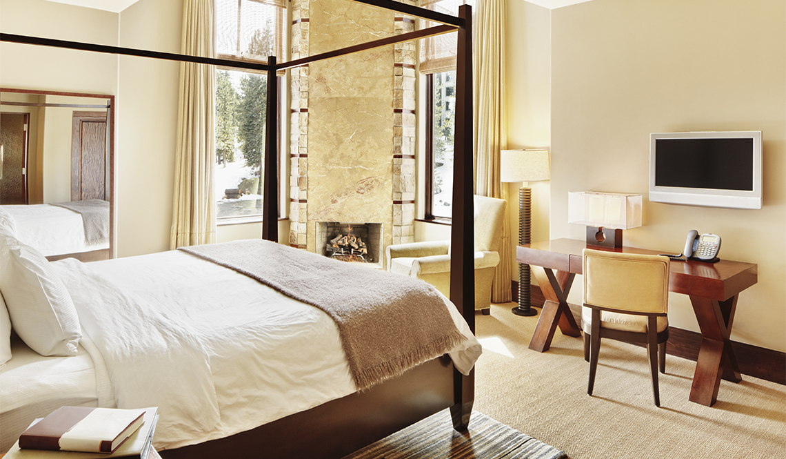 item 8 of Gallery image - Hotel room with a bed on the left and a desk and TV on the right