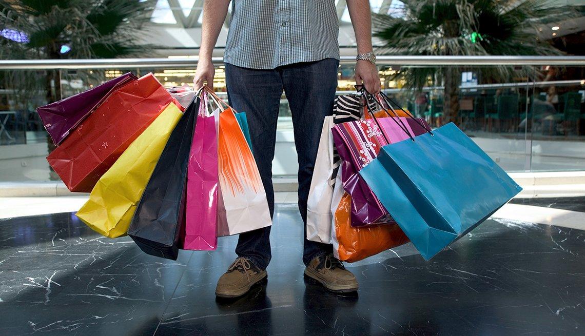 Hombre sosteniendo bolsas de compras de diferentes tiendas