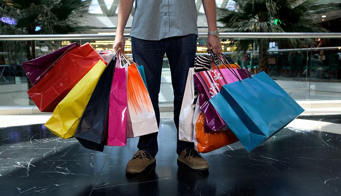 man holding an large amount of shopping bags