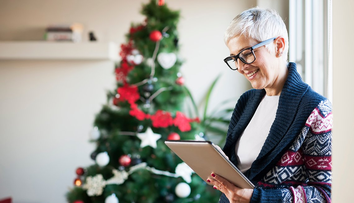 Mature woman at home shopping on tablet with Christmas tree in the background