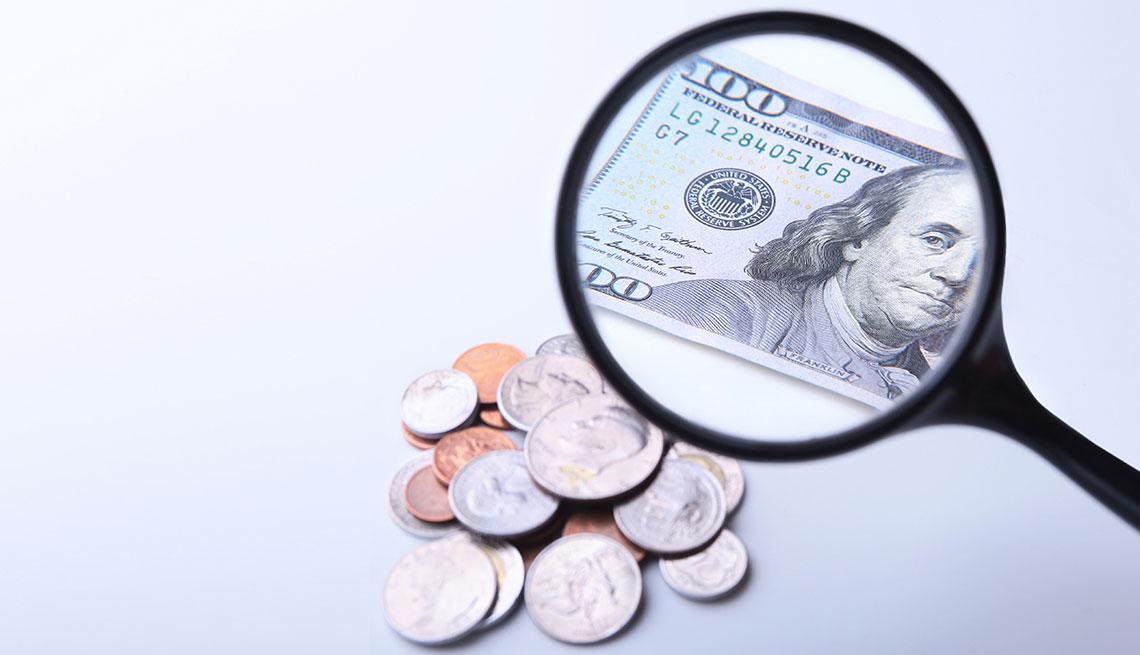 Monedas y un billete de 100 dólares visto a través de una lupa
