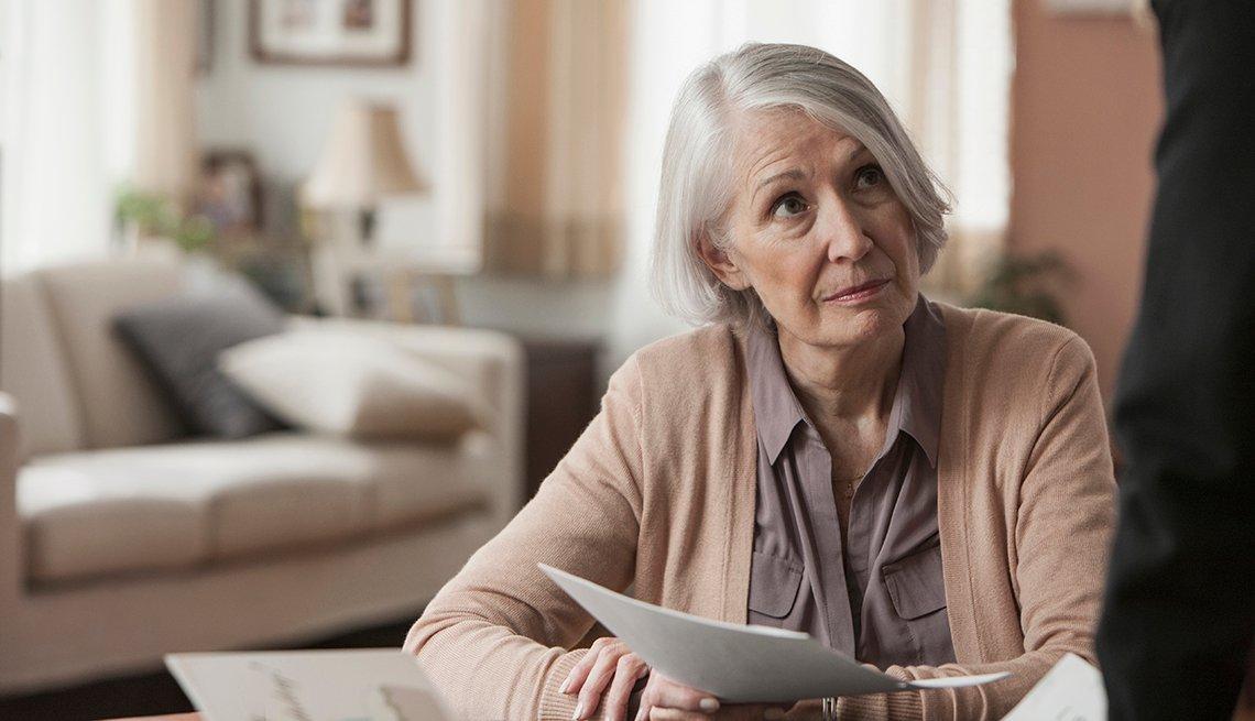 Mujer mayor con documentos en la mano y con cara de preocupación