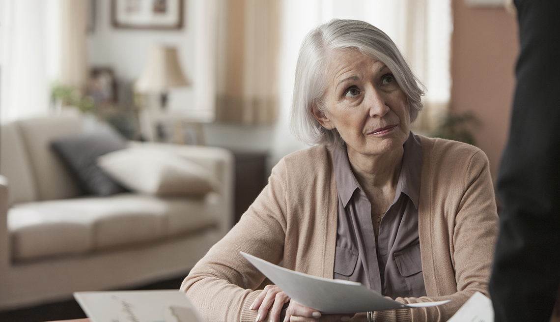 Mature woman holding paperwork looking concerned