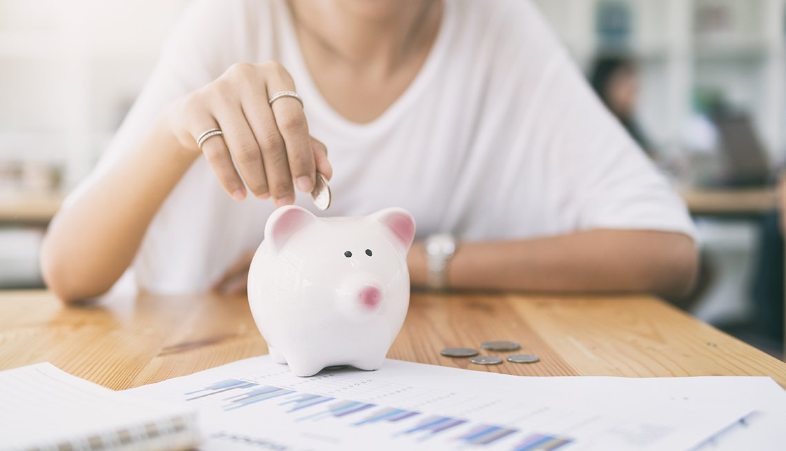 woman putting money in white piggy bank