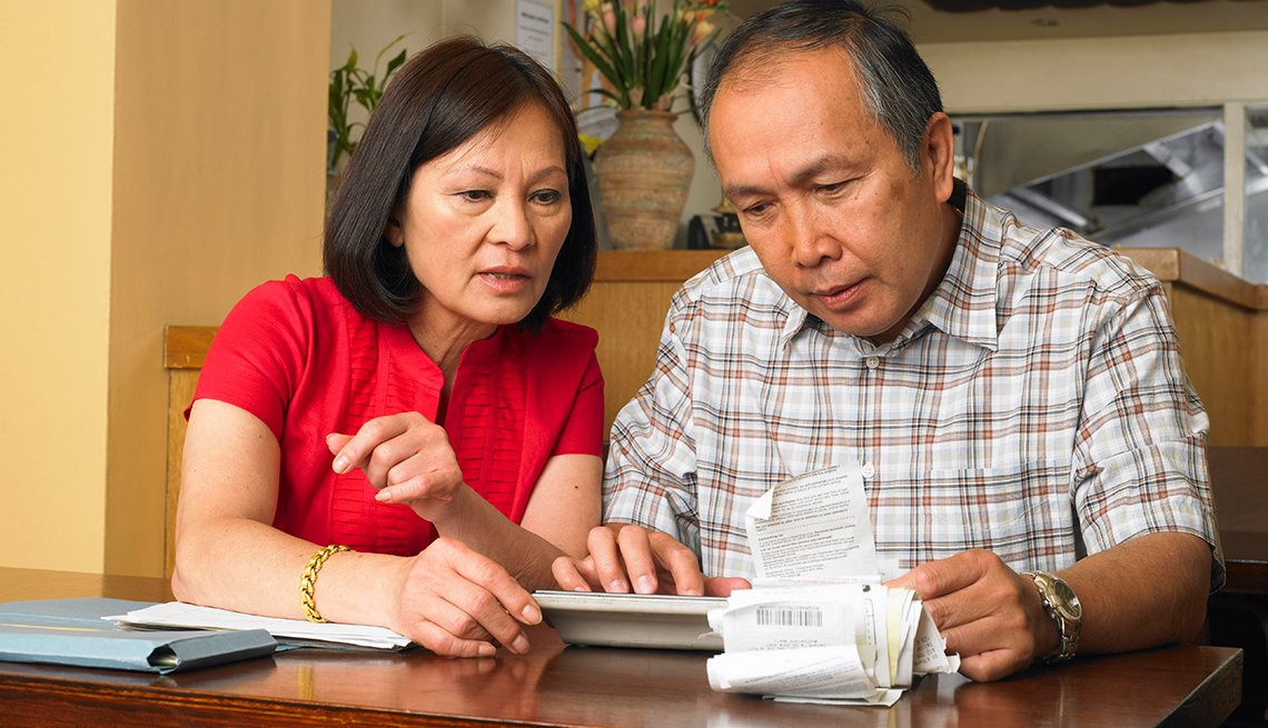 A couple sitting at a table reviewing receipts