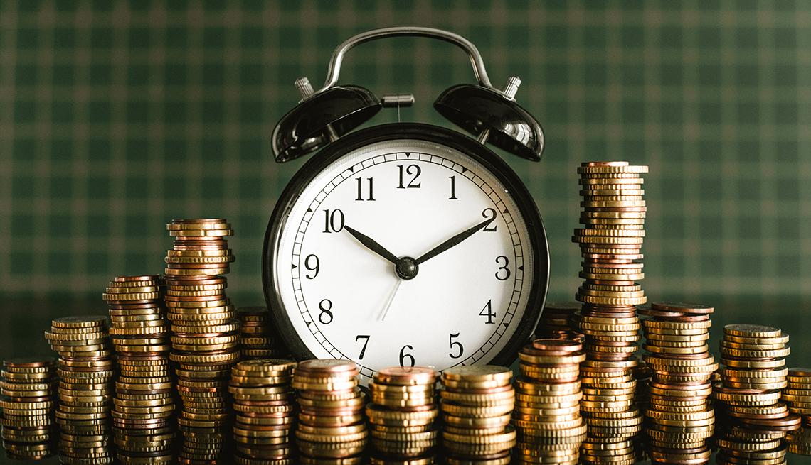 Reloj de mesa con campanas rodeado de monedas