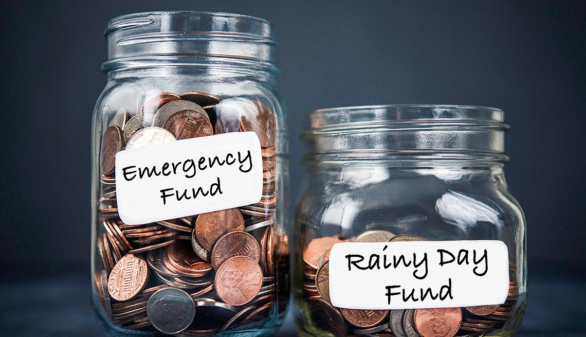 two jars filled with coins. One jar is larger and is labeled emergency fund, the other jar is smaller and contains fewer coins. it is labeled rainy day fund