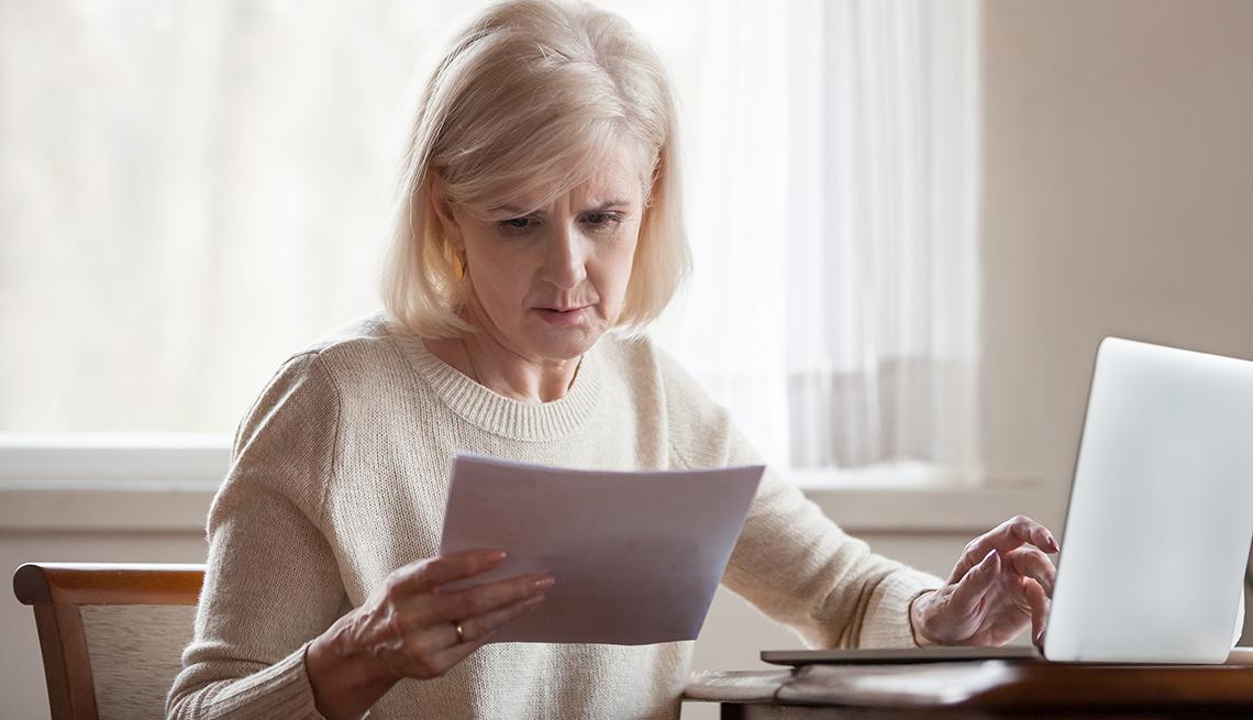 Mujer sosteniendo facturas en una mano y con la otra en la computadora.