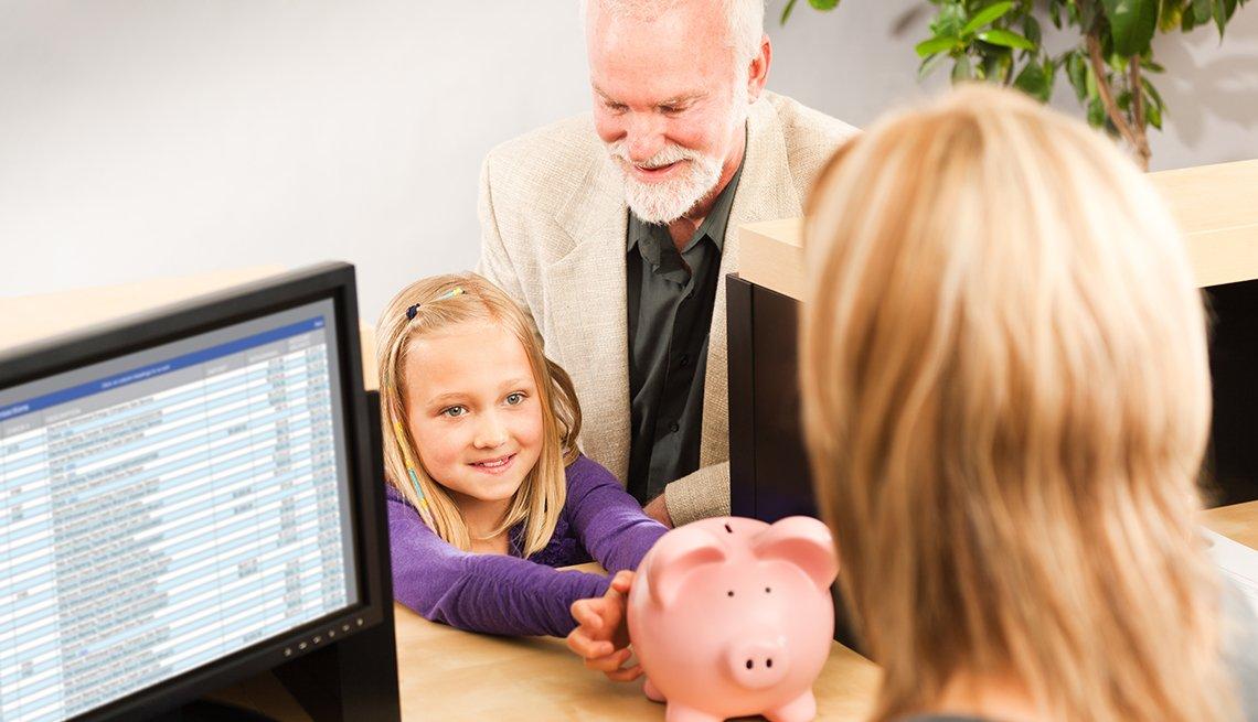 Abuelo lleva a un banco a su nieta quien abre una cuenta con su alcancía.