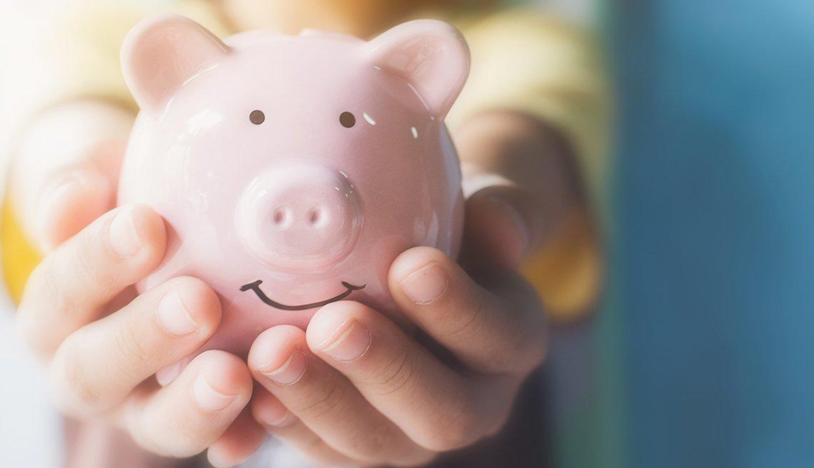 A person holding a pink piggy bank