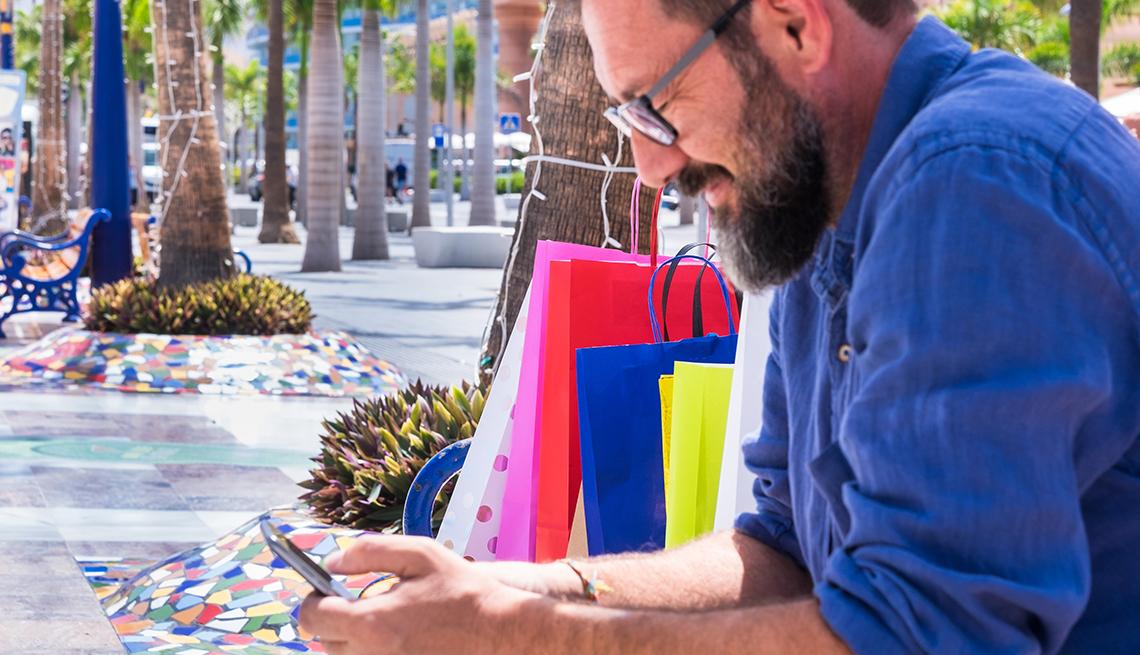 Hombre sentado en una banca con bolsas de compras y viendo su teléfono móvil.