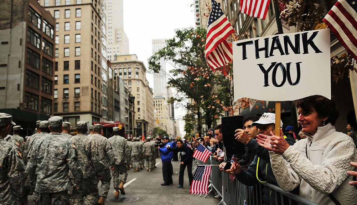 Una mujer sostiene un cartel que dice gracias en inglés durante un desfile de veteranos