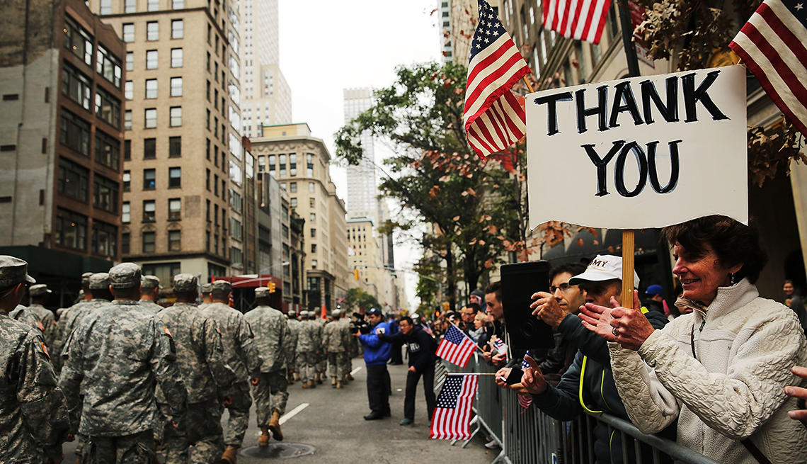 A woman holds a sign that says thank you at a parade for veterans