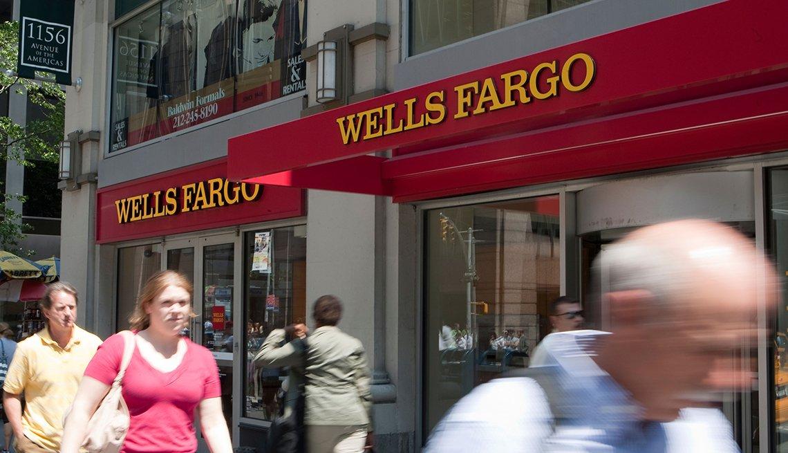 Personas caminando frente a una sucursal de Wells Fargo.