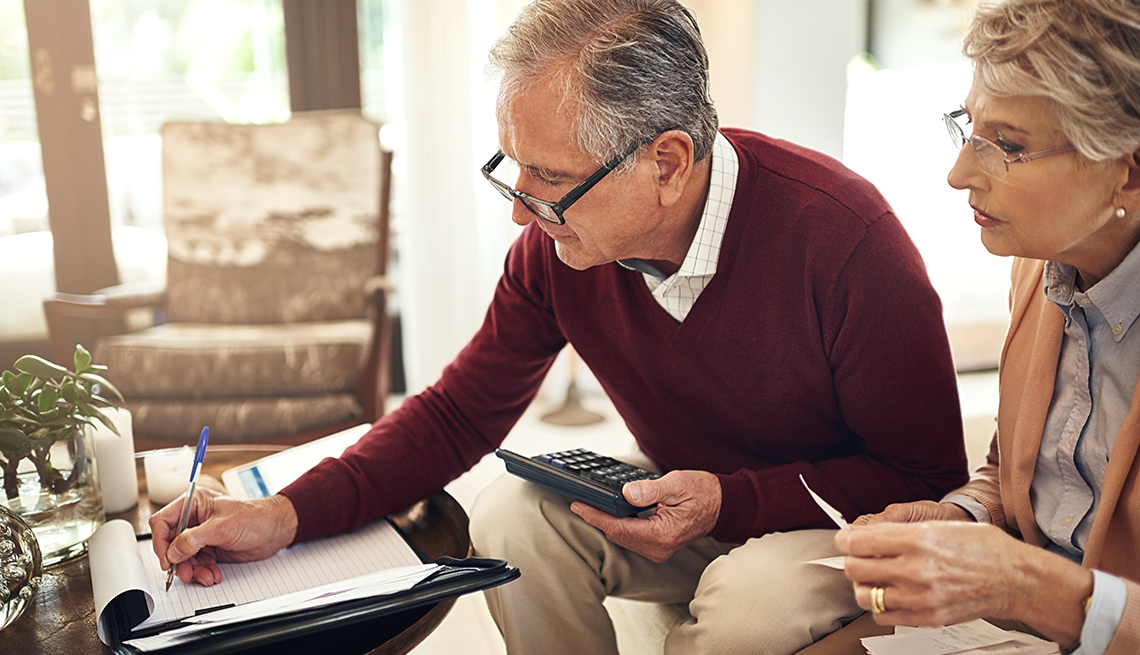 senior couple writing notes to keep track of budget expenses while sitting on the living room sofa