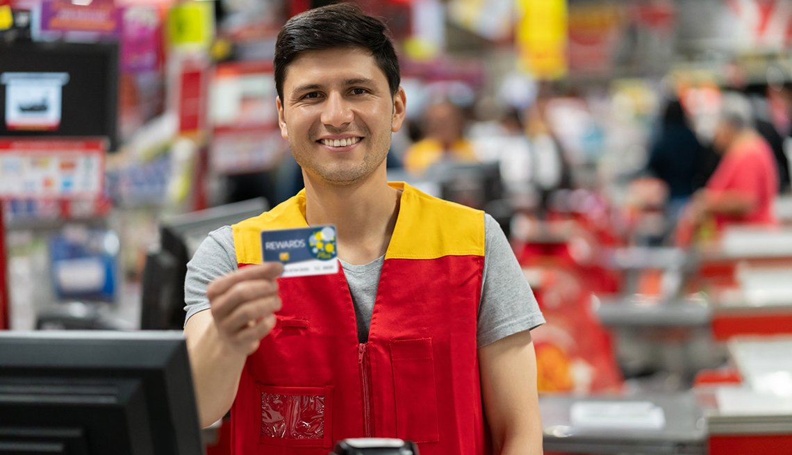 Cashier at a home improvement store holding a rewards card