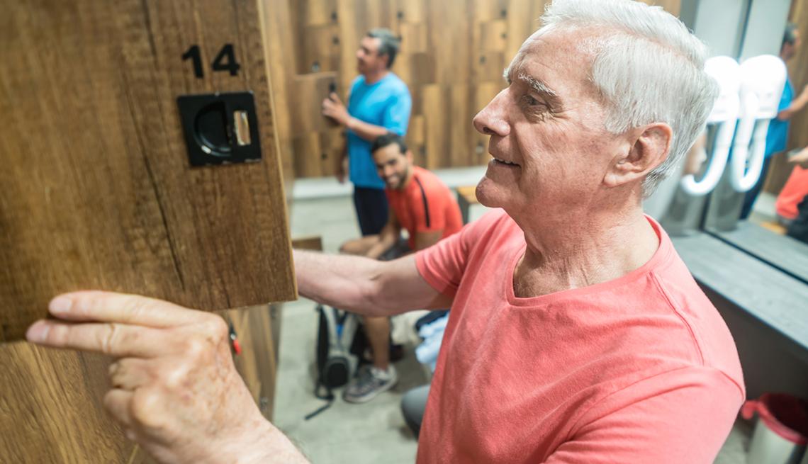 Señor mayor abriendo un casillero en el baño de un gimnasio.