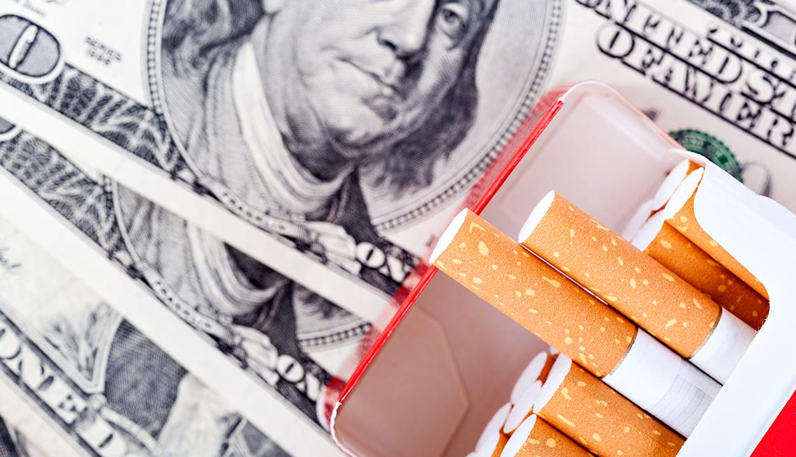Caja de cigarrillos abierta y billetes de 100 dólares al fondo.
