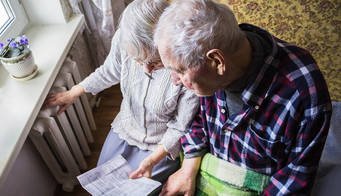 Senior couple hold gas bill and check radiator