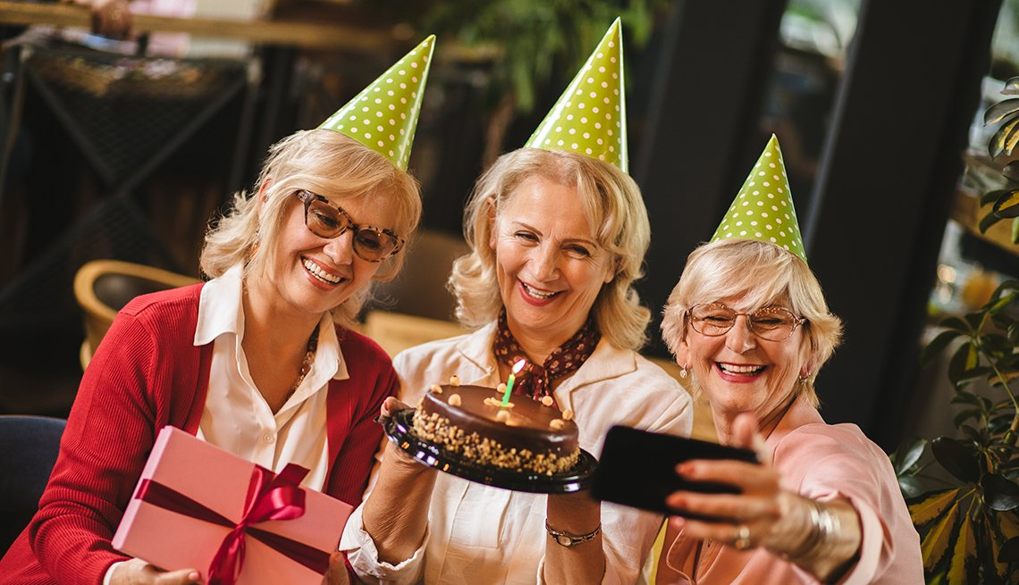 Senior ladies taking selfie while celebrating birthday in cafe with cake and gifts