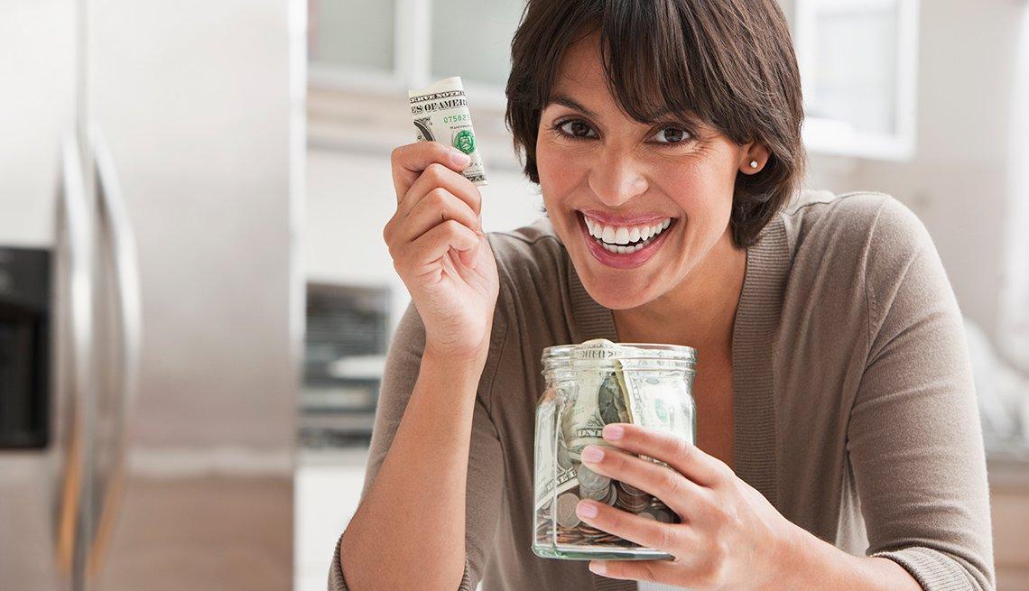 Mujer sosteniendo billetes de dólares en sus manos.